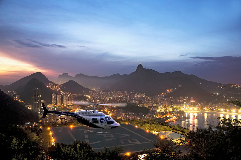 Panoramic view of Rio de Janeiro from sugarloaf mountain. Corcovado can be seen in the distance.  Also visible, hillicopter pad with helicopter taking off and Flamengo beach area (far right). Photo by Christian Wilkinson.