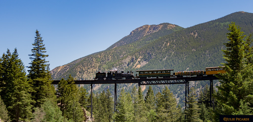 A really tall trestle in front of some huge mountain peaks makes our train look like a toy.