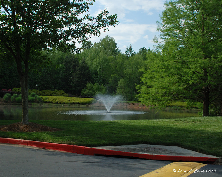 A fountain in a small pond on the back side of the property