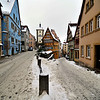 Snowy cobblestone streets in Rothenburg, the Plönlein/Siebers Tower on the left and the Kobolzell Gate on the right.