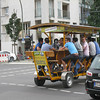 "Berlin - near Checkpoint Charlie.  The ""Beermobile"".  This unusual contraption drove by while I was touring the area.  It appeared that all of the pedallers had a Beer in front of them."
