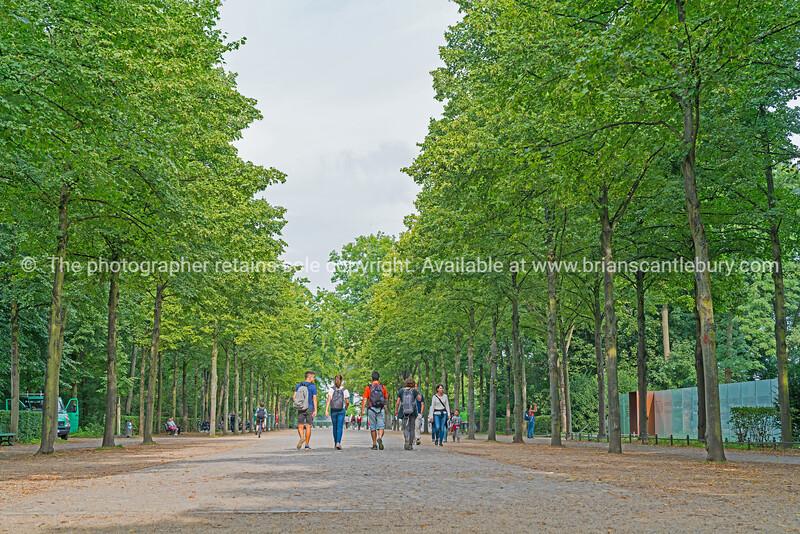 People walking through Tiergarden towards Brandenburg Gate in Berlin.