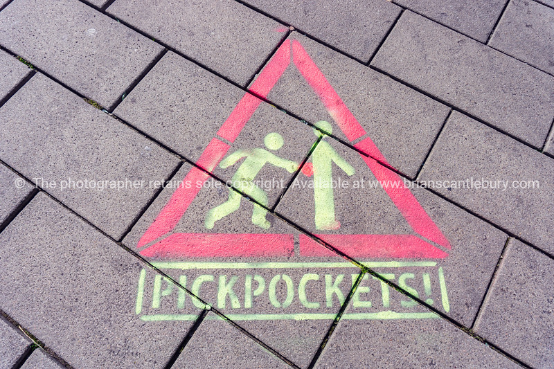Public warning sign on pavement advising to beware Pickpoctkets.