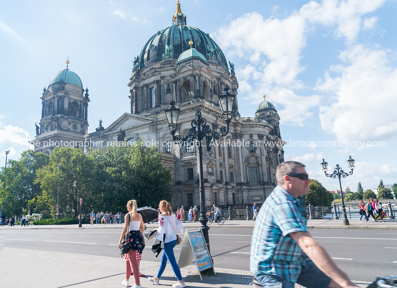 BERLIN, GERMANY - AUGUST 28, 2017; Tourists pass on street outside historic Berlin Cathedral on one end Museum Island example of Baroque architecture is biggest protestant cathedral in the city.