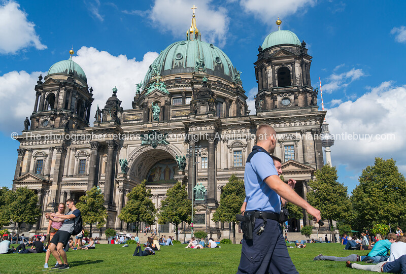 BERLIN, GERMANY - AUGUST 28, 2017; People relax in sun on lawn as tourists take selfie and police pass  Berlin Cathedral on one end Museum Island example of Baroque architecture is biggest protestant cathedral in the city.