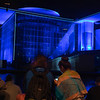 Blue  light effects of buildings beyond tourists  in foreground sitting looking across  in Government District Berlin