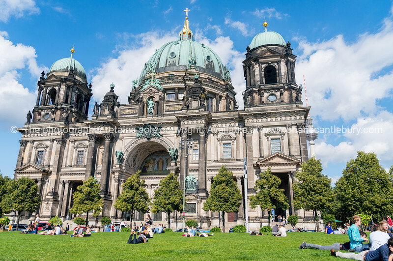 People relax in sun on lawn outside Berlin Cathedral