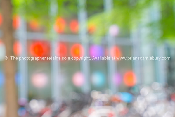 Urban abstract architecture, bicycles  and  multi-color lights  and greenery of tree leaves in background image