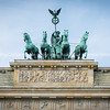 bronze statue four hourses pulling chariot on top of the Brandenburg Gate