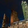 Relics or portions of Berlin Wall on display in street below entrance to Potsdamer Platz underground against backdrop three illuminated ultra-modern office towers and dark night sky.