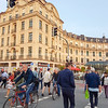 People crossing street on foot and riding bicycles  to and from Karlsplatz  on foot and cycle