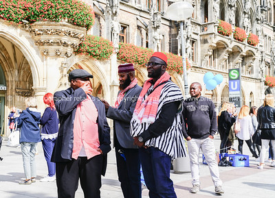 Three ethnic black African men in group and traditional dress talk together  in city central square
