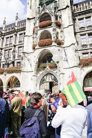 protestors march through tourists in city central square below the gothic city hall.