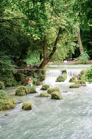 Woman in mermaid suit sits on rock in Eisbach River by waterfall.