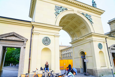 Ornate architectural detail  of wall and arched entrance with pretty girl sitting niche twisting hair by hire bicycles.