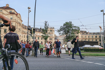 Group of people gather and start to cross when lights change crossing light on Karlsplatz in city center.