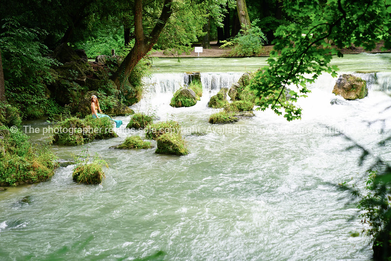 Woman in mermaid suit sits on rock in Eisbach River by waterfall surround by nature.