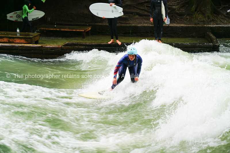 River surfers on Eisbach River in middle of European city.