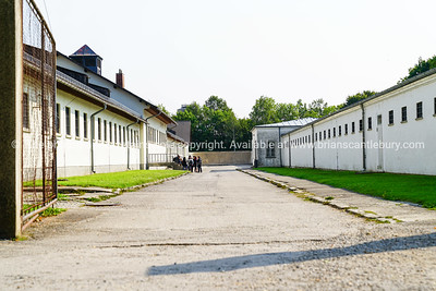 Grim looking yard between cell blocks of Dachau Concentration Camp with group of tourists gathered in distance