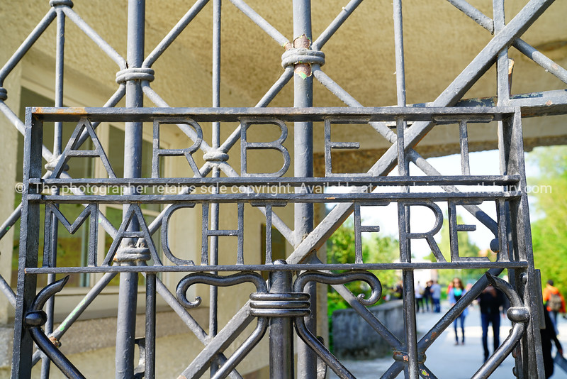 Tourists arriving defocused through wrought iron gates of Dachau Concemntration Camp.