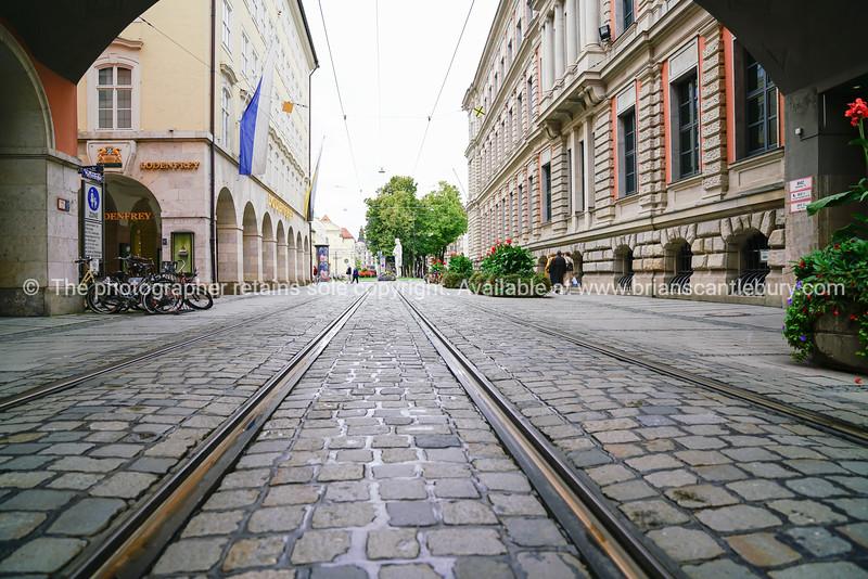 Railway tracks run through cobblestone street between city buildings