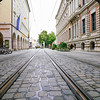 Railway tracks run through cobblestone street between city buildings