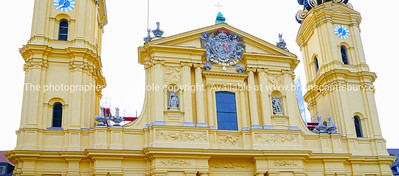 Ornate architectural detail  close-up with clock towers statues and coat of arms on yellow neo-gothic style city building