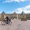 Blurry image of man cycling past large cobblestone courtyayd surrounded by historic building