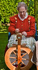 An old, grumpy grandma behind a spinning wheel