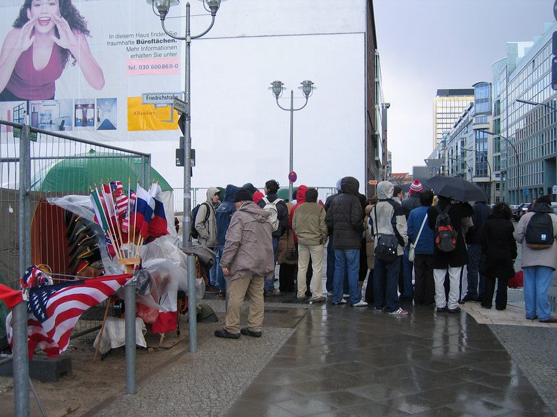 Crowds of tourist pack the street where the Checkpoint Charlie museum, few noticing that the direction where the wall actually runs...