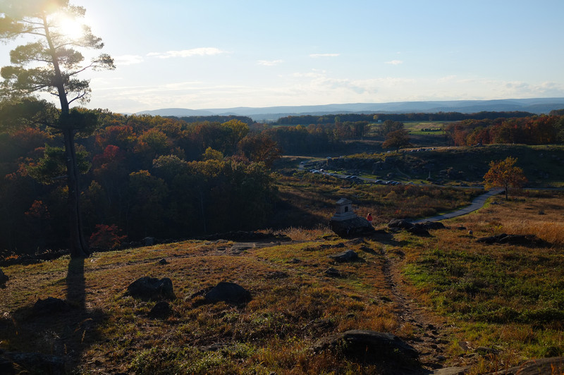 © Mark J. Lucas<br /> <br /> The Union view from atop Little Round Top looking west along the southern end of Cemetery Ridge.  From this vantage point along the tree line and where the cars are located is where the advance from the Confederate solders took place.  It was here and to the right (north) that perhaps the most famous aspect of the Battle of Gettysburg took place.  And that was the attack from the Confederate forces known as Pickett's Charge in which the Rebels marched along open field under fire towards the dug-in Union forces along high ground.  It was a defeat for the South and marked the turning point in the war.