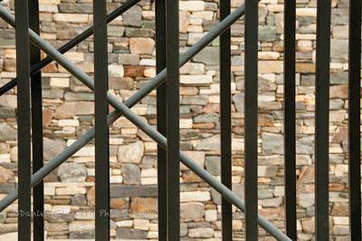 Metal bars in front of a stone wall of the Frank Russell Threshold building in Gig Harbor, Washington.