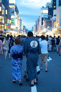 A pretty typical Japanese couple heading to the festival. The guy's fan has a picture of one of the Gion Festival floats.