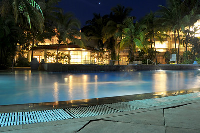 With the moon rising in the sky, the pool side at the Club Mahindra resort at night in Goa, India.