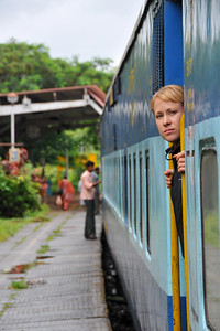 Passengers looking out of the train at the station.  Train ride from Mumbai to Goa, India during the rains