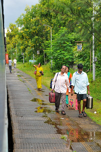 Passengers getting off. Train ride from Mumbai to Goa, India during the rains