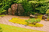Quintessential Japanese Garden features the tiny stone bed and the large rock focal.