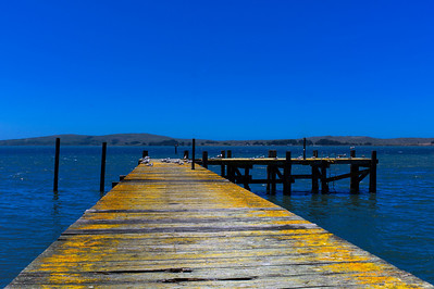 A decrepit old pier jutting out into Bodga Bay.