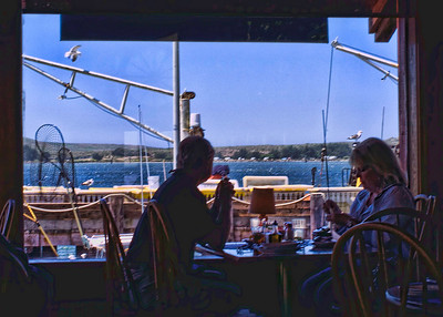 A couple enjoying their meal and the views across the water.