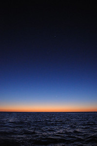 "March 2012 Sea of Cortez Sunset, the crescent new moon is that white speck above the orange horizon, and Jupiter and Venus are the first 2 ""stars"" out above the moon."