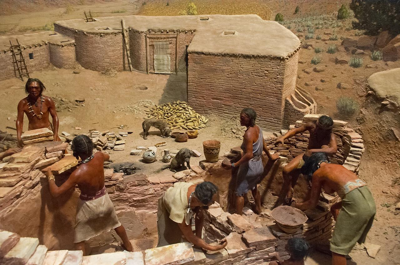 Museum diorama showing Native Americans building a pueblo.