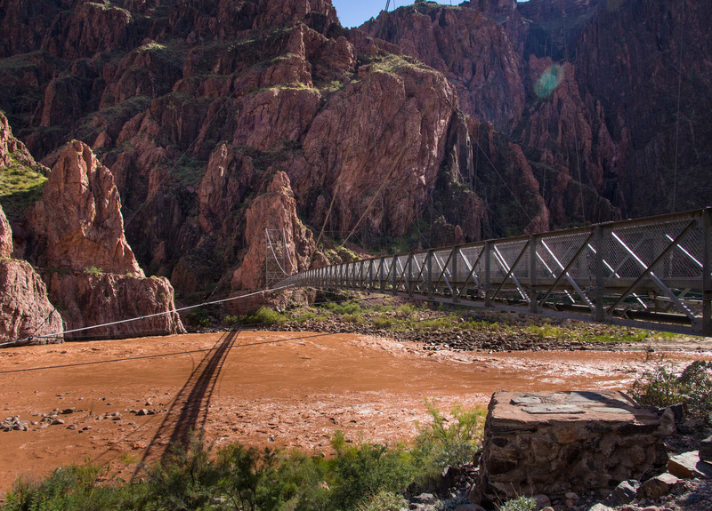 The silver bridge spanning the Colorado river, used for people only. This is the normal color of the river. There is a black bridge 1/2 mile up river used by people and mules.