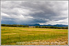 Farmland with a rainstorm in the distance, located in Utah