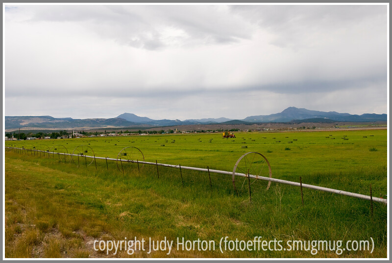 A hay baler works in a farm field in Utah