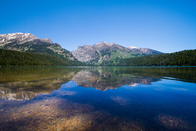 This scenic, 3-mile loop tours a wide range of ecosystems in the Laurance S. Rockefeller Preserve, a 1,106-acre ranch donated to Grand Teton National Park and opened to the public in June 2008. From the parking area, follow a winding gravel path through a sagebrush meadow and past an aspen grove to the visitor center—step inside the center to view multimedia exhibits on the preserve.<br /> <br />  From here, the trail winds through forests of lodgepole pine, Douglas fir, and blue spruce, and parallels Lake Creek. Listen for the high-pitched cries of elk, and watch for deer and Clark's nutcrackers. After 1.5 miles, the path traces the southern shore of Phelps Lake, offering spectacular views of the Tetons and the lake, before turning south for the trip back to the trailhead.