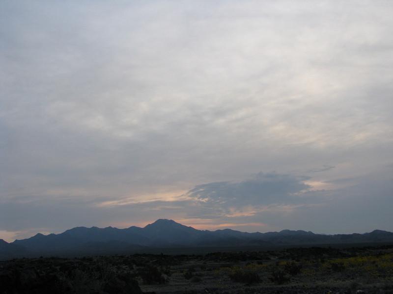 A dawn sun doing battle against the shroud covered sky.