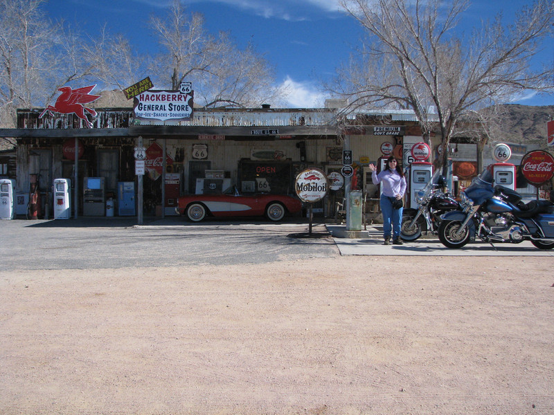 Julie standing by old gas pumps and motorcycles in front of the general store.