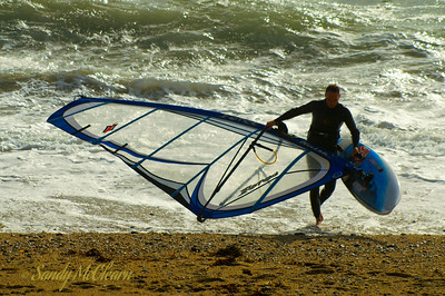 A windsurfer walks out of the water of Mounts Bay in Cornwall, England, onto a beach near Penzance.