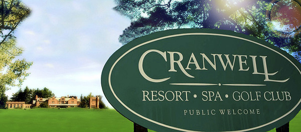 Sign for the Cranwell Resort, Spa, and Golf Club with Wyndhurst in the distance.