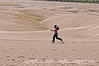 A woman runs across some of the sand dunes at the Great Sand Dunes National Park in Colorado